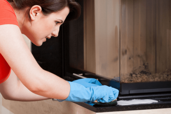Image of a woman cleaning a gas fireplace